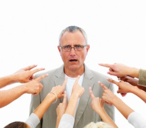 People pointing towards a senior business man